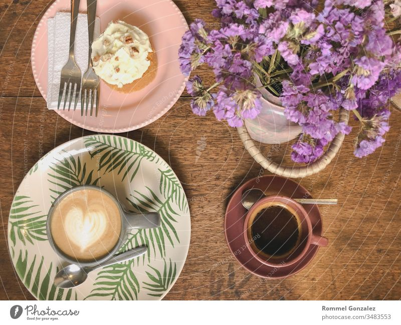Cup of cappuccino with latte art and xpresso on a wooden plate and wooded table decorated with dried flower, Selective focus, Soft focus celebration piece fork