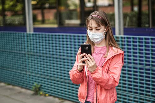 Portrait of a young girl with a protective mask looking into her smartphone, biological danger from the corona virus person Epidemic Protection Virus flu