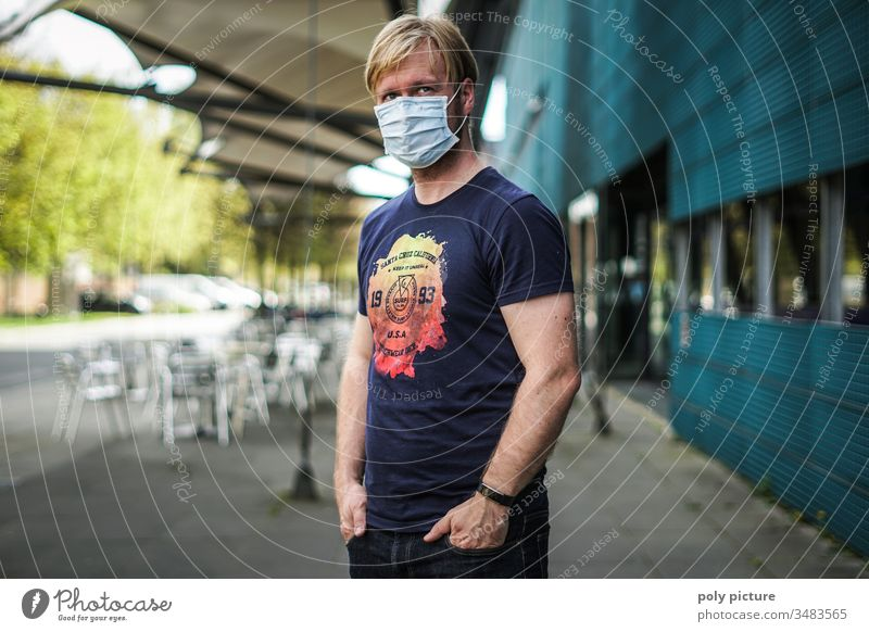 Portrait of a man with a protective mask standing in front of a building, biological danger from coronavirus: Covid-19 danger person Epidemic Protection Virus
