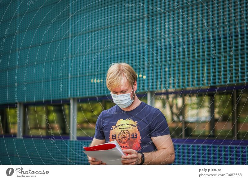 Portrait of a man with a protective mask who read a report, biological danger by coronavirus: Covid-19 danger person Epidemic Protection Virus flu