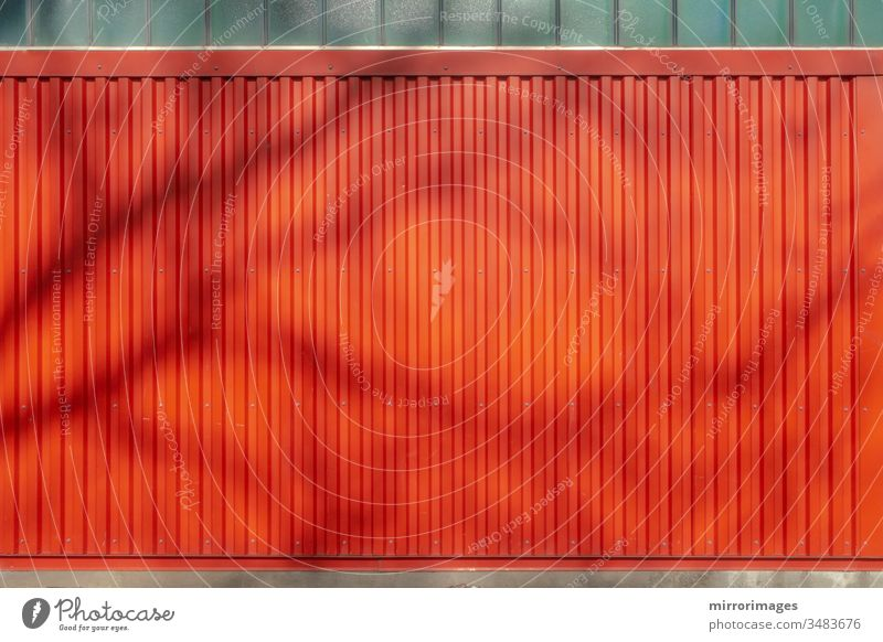 outdoor weathered vertical red wall siding background backdrop with tree shadow siding texture metal texture grooved aluminum industrial stripes lines metallic