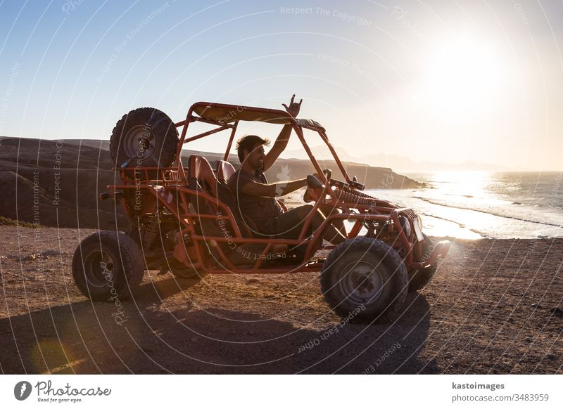 Man driving quadbike in sunset. beach adventure extreme sand sport vehicle outdoor fun ride ocean show rocking sign male quad racing dune buggy land vehicle