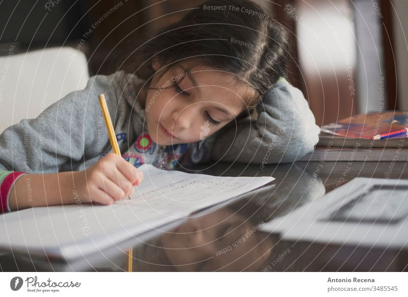 Seven years old girl doing homework at home education student writing 7s sitting people person kid pencil child childhood children candid focus in foreground