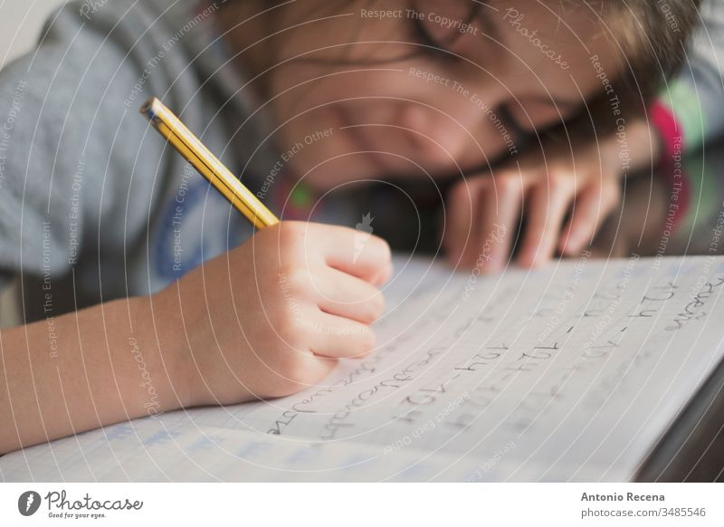 Little seven years old girl doing homework education student writing 7s sitting people person kid pencil child childhood children candid one concentration