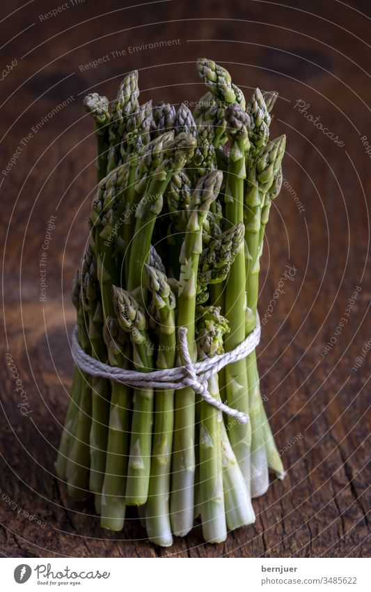 fresh green asparagus on dark wood Asparagus Bundle Asparagus bundle plank Wood Holiday season seasonal Gourmet string Kitchen Ingredients antioxidant