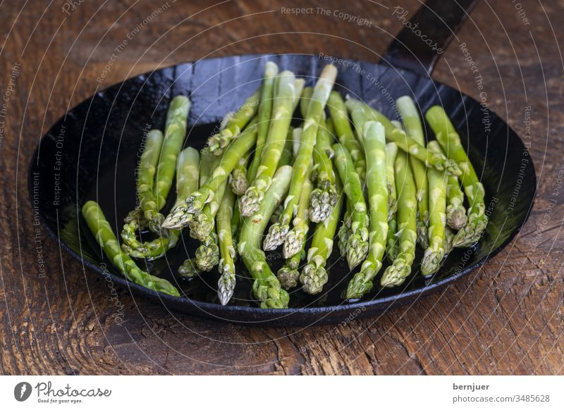 fresh green asparagus in a pan on dark wood Asparagus Pan Asparagus pan plank Wood Holiday season seasonal Gourmet string Kitchen Ingredients antioxidant