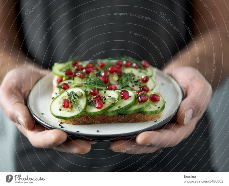 Vegan sandwich with cucmber in male hands vegan toast veggie plate plant-based cucumber pomegranate ready-to-eat ideas healthy breakfast lunch snack concept