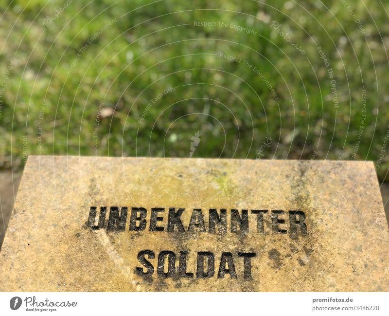 "Gravestone with inscription ""Unknown Soldier"" War World War Tombstone Green Meadow Stone Capitalism neoliberalism arms deals Death wound war trauma war traumas"