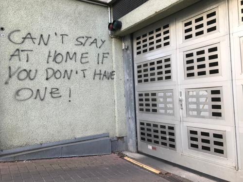 "Graffiti: ""Can't stay at home if you don't have one"" protest Demonstration Wall (building) house wall Garage garage entrance policy Economy Company Homelessness"