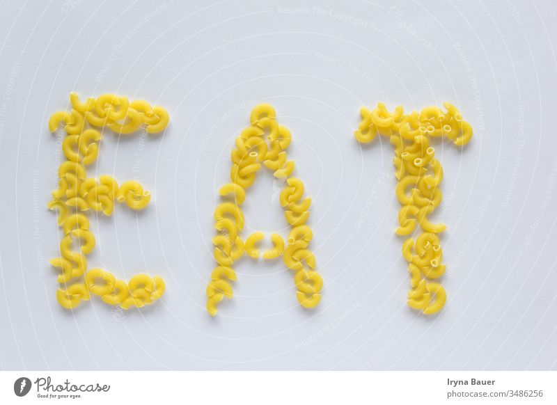 Word eat from uncooked yellow pasta on the white bachground. menu food kitchen word macaroni italian eating raw penne foods health texture isolated background
