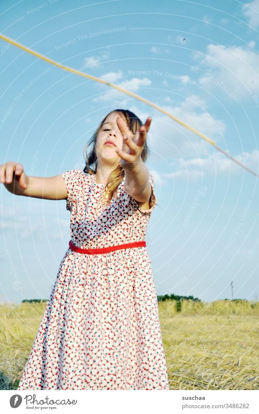 girl in summer dress reaches for a straw Child Girl Summer Field acre Summer dress Catch Grasp Action grasp at straws symbol symbolic