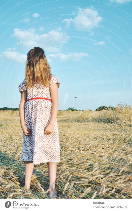 girl in summer dress on a straw chopper with hair on her face Child Girl Summer Field acre Summer dress Infancy Hand Fingers Arm Sky Grain field Wild Movement