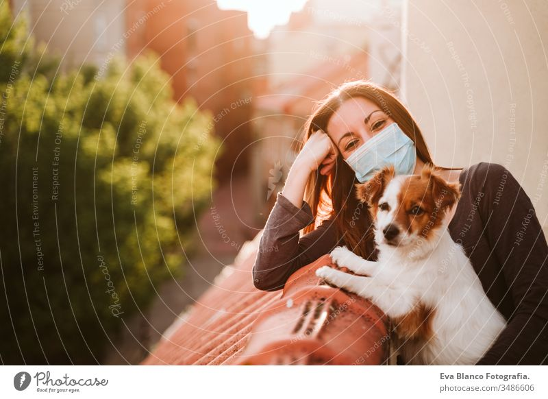 young woman at home on a terrace wearing protective mask. Hugging her cute jack russell dog. Corona virus Covid-19 concept pet coronavirus covid-19 indoors