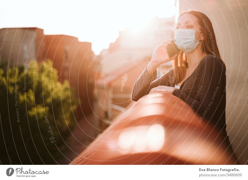 young woman at home on a terrace wearing protective mask, using mobile phone and enjoying a sunny day. Corona virus Covid-19 concept smart phone technology
