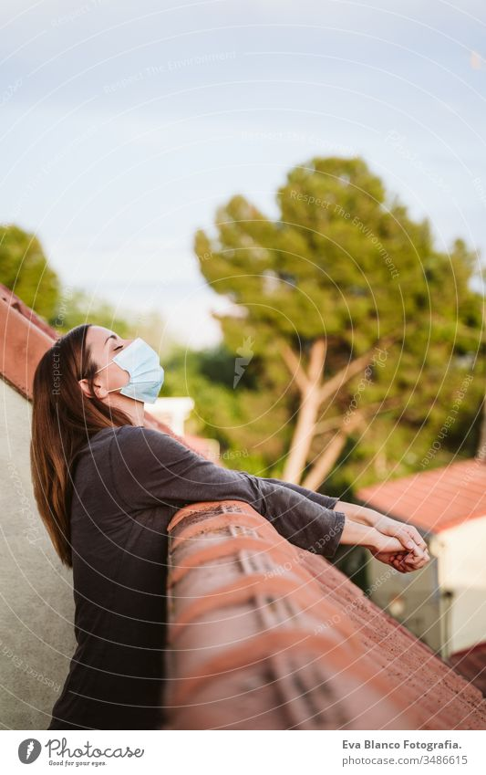 young woman at home on a terrace wearing protective mask and enjoying a sunny day. Corona virus Covid-19 concept coronavirus covid-19 indoors caucasian