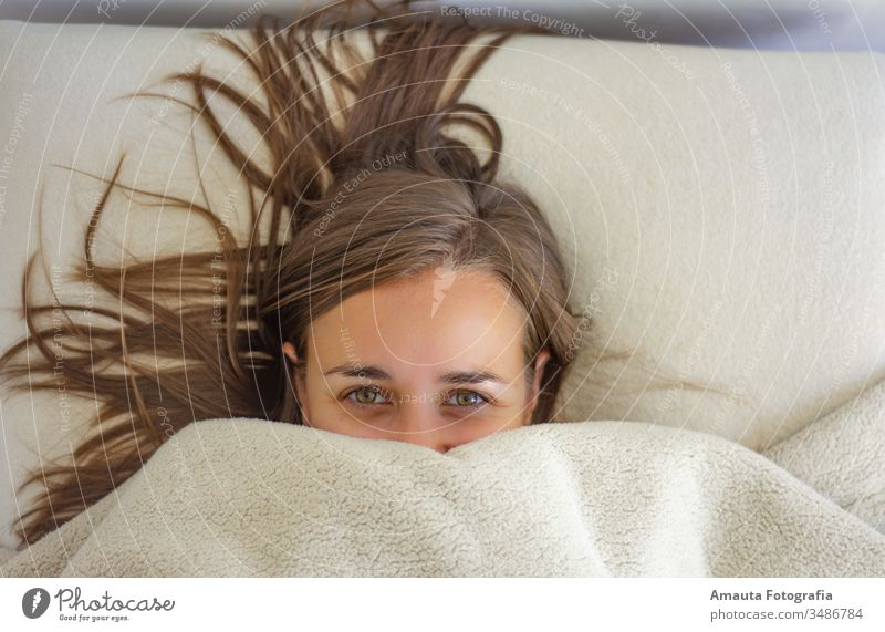 Woman in bed covered up to the face awake beautiful bedroom bedtime blanket carefree closed comfort comfortable cozy cute daydreaming eyes girl hair half face