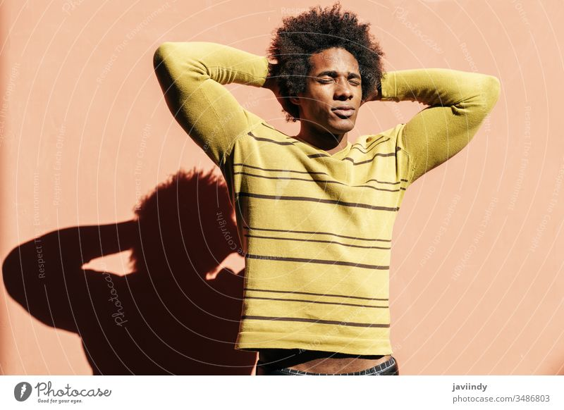 Cuban black man enjoying the andalusian sun with his eyes closed millennial afro sunlight hair african male face adult portrait american person casual guy
