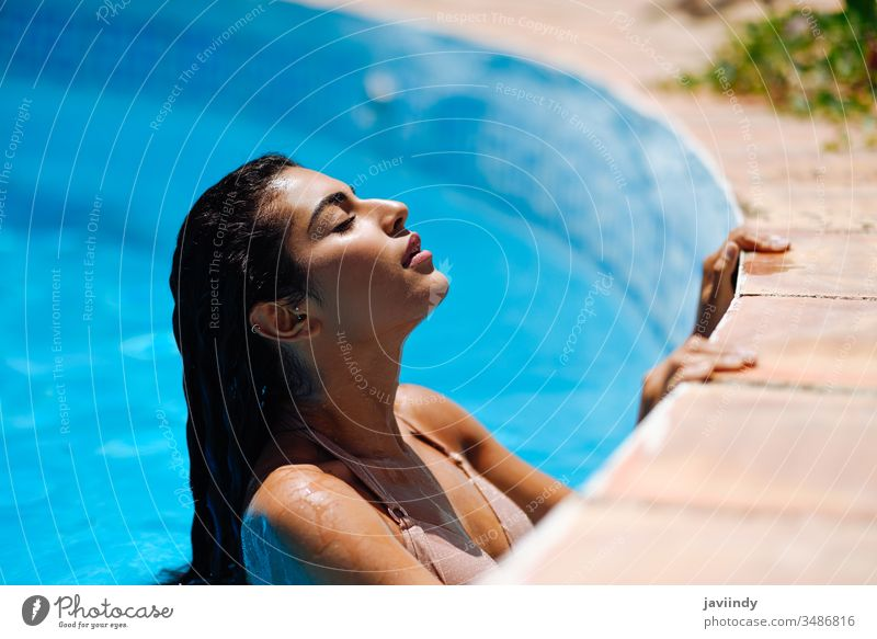 Beautiful Arab woman relaxing in swimming pool. summer beautiful bikini young water girl female sunbathing beauty body attractive sunny resort tanned happy