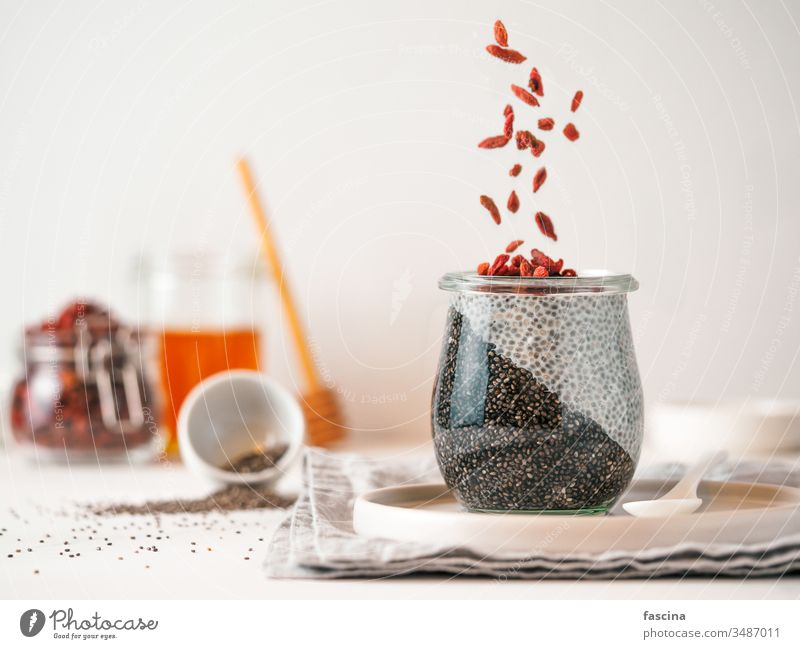 charcoal two colors chia pudding with goji , copy space goji berries black glass idea white fresh breakfast dessert food healthy seed vegan berry diet dairy