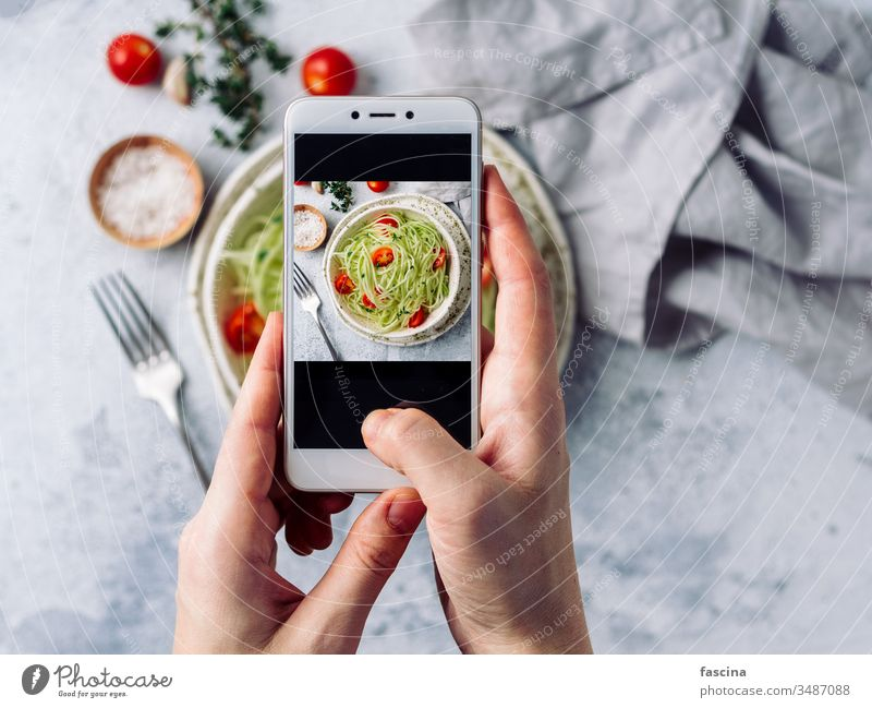 Zucchini noodles salad. Top view, copy space smartphone photography woman hand hold take social raw zucchini zoodles spaghetti diet food fresh healthy lunch