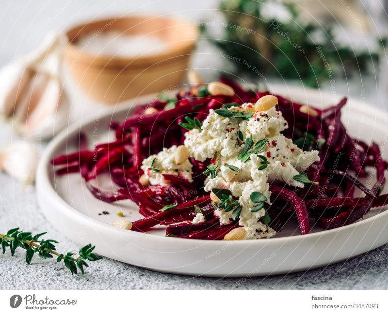 Raw beetroot noodles or beet spaghetti salad nuts raw pine nuts thyme diet food fresh healthy lunch plate preparation vegan vegetarian appetizer dish vegetable