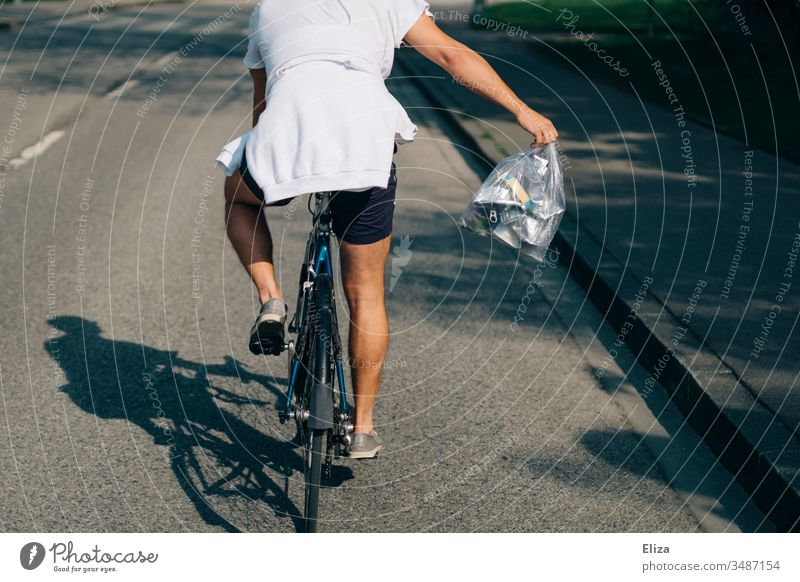 A man in summer on a bicycle with a bag full of metal garbage taking away garbage; recycling, waste separation Metal waste Recycling Bicycle cyclist Man Summer