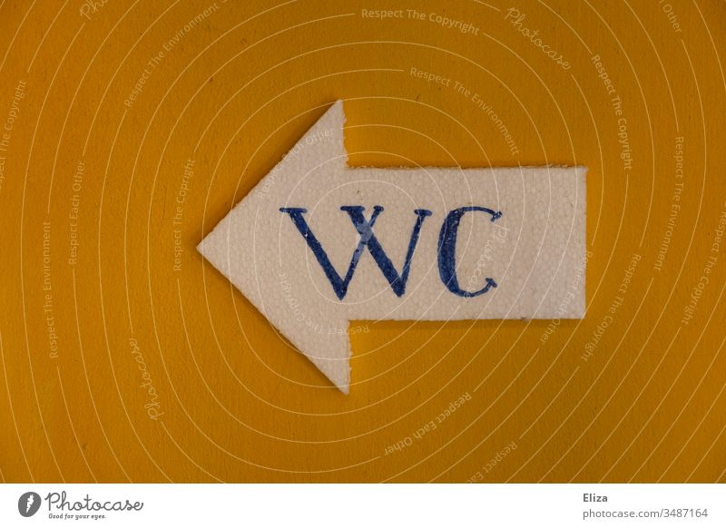 A yellow wall on which a sign in the shape of an arrow with the word WC hangs LAVATORY Arrow Toilet Yellow Wall (building) Letters (alphabet) Word Signage
