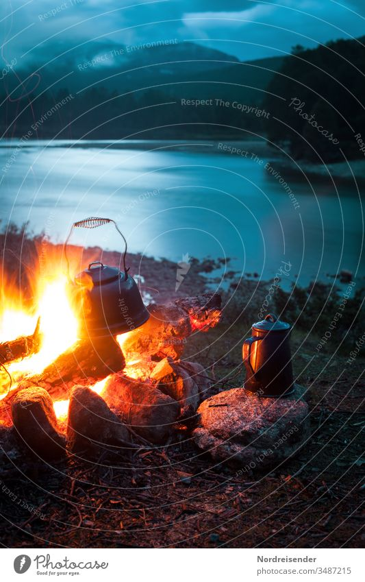 Campfire with coffee pot and kettle at a river in the wilderness at night campfire Coffee Coffee pot Water River outdoor Evening Night blue hour Wilderness