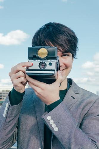 Young Mixed Race Photographer with Polaroid Camera on River Thames photographer smiling polaroid vintage business tourist young travel europe vacations
