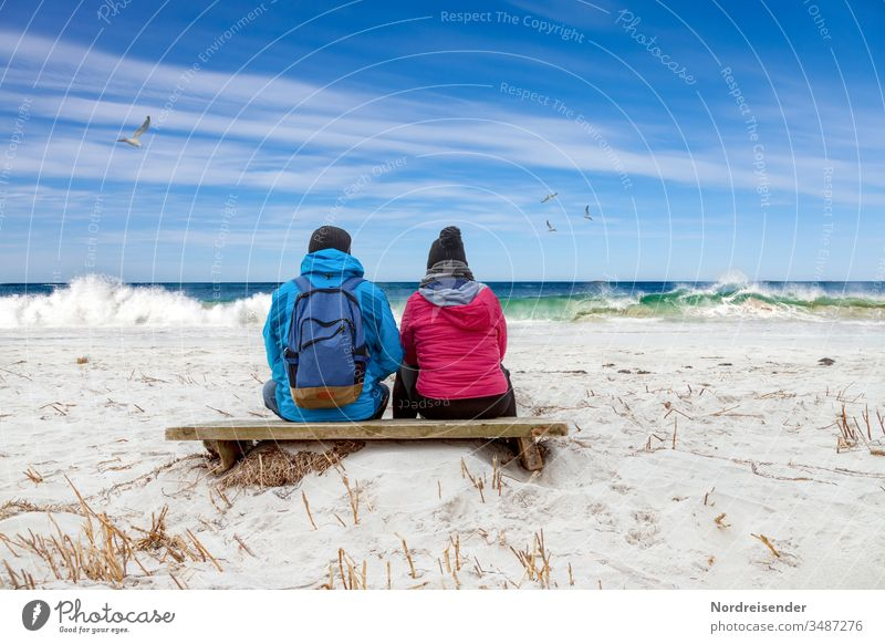 Dreamy couple looking at the waves on the beach of the Baltic Sea Ocean Beach Woman Man North Sea Sit Break Hiking free time Couple Family together beach hike