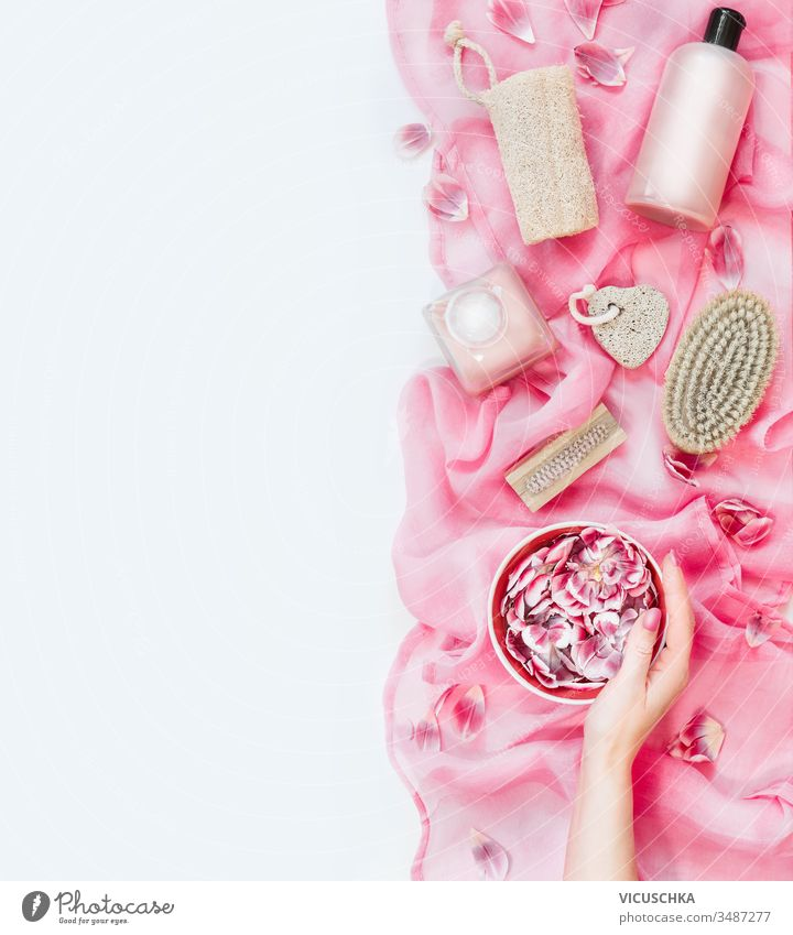 Female hand holding water bowl with flowers on pink towel with various eco friendly skin care and beauty tools: brush, sponge, pumice and cosmetic products on white background. Top view. Flat lay
