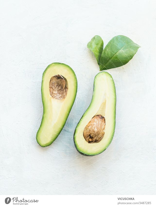 Avocado cut in half with green leaves on white table background, top view. Healthy food ingredient avocado healthy food antioxidant refreshment nutritious