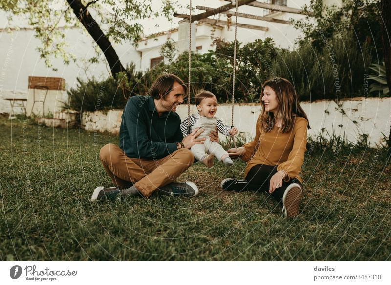 Father and mother swinging their baby sitting on the green grass in the park. Infant is laughing happy. excitement enjoyment smiling care innocent smile love