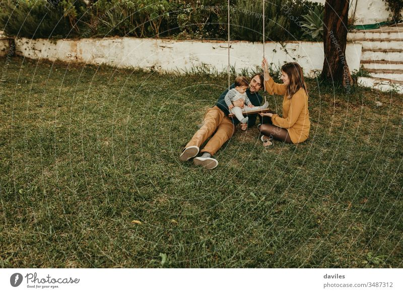 Beautiful couple enjoying with their baby son in a swing, on the green grass of the garden at the countryside excitement enjoyment smiling sitting care innocent