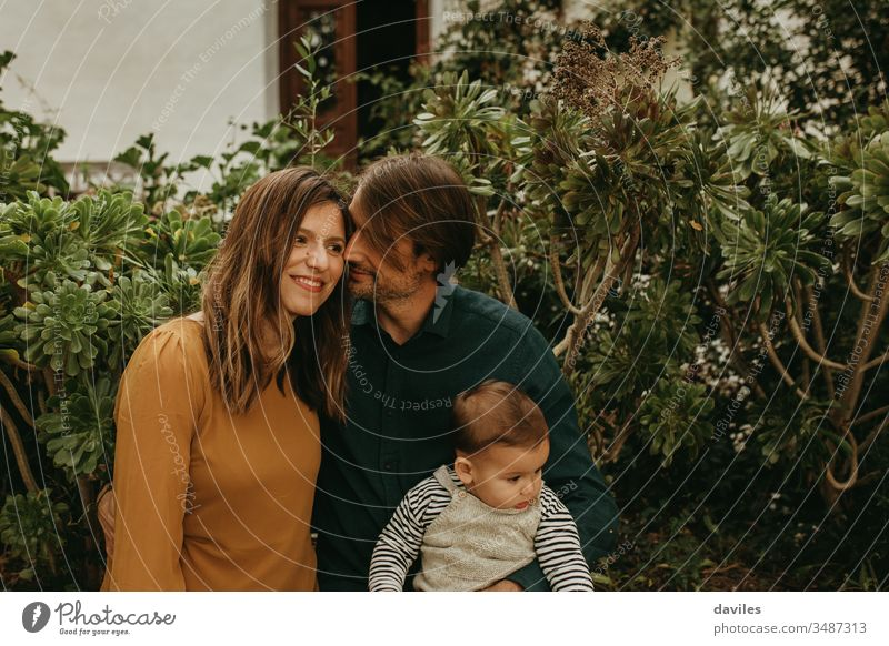 Lovely couple standing together while man holds their baby son alternative indie hipster smile woman dad parents portrait outdoors garden lifestyles wife