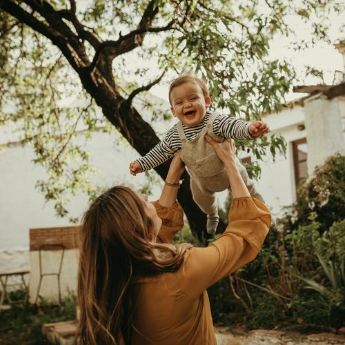 Mother holding her baby son up in the air, and baby laughing. playing adult fly arms throwing enjoying parenthood blond garden tree life woman newborn outdoors
