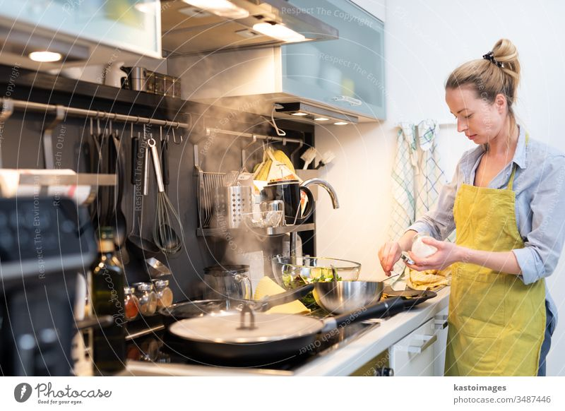 Stay at home housewife woman cooking in kitchen, salting dish in a saucepan, preparing food for family dinner. young healthy meal person vegetable female