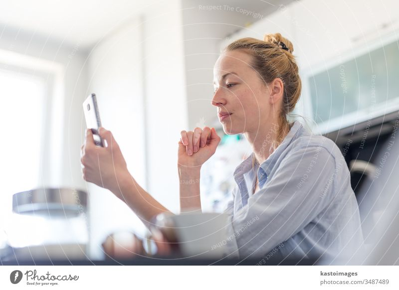 Young pleased woman indoors at home kitchen using social media apps on mobile phone for chatting and stying connected with her loved ones. Stay at home, social distancing lifestyle.