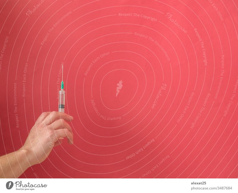 Hand with syringe on red background with copy space antibiotic coronavirus covid-19 disease dose drug epidemic equipment hand health healthy hospital illness