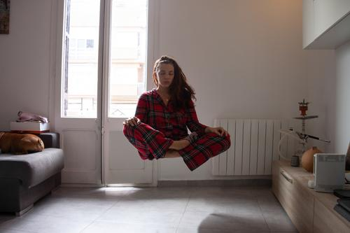Young woman with pijama meditating while levitating at home harmony floating spirituality contemplation young concentration fly meditation sexy indoors girl