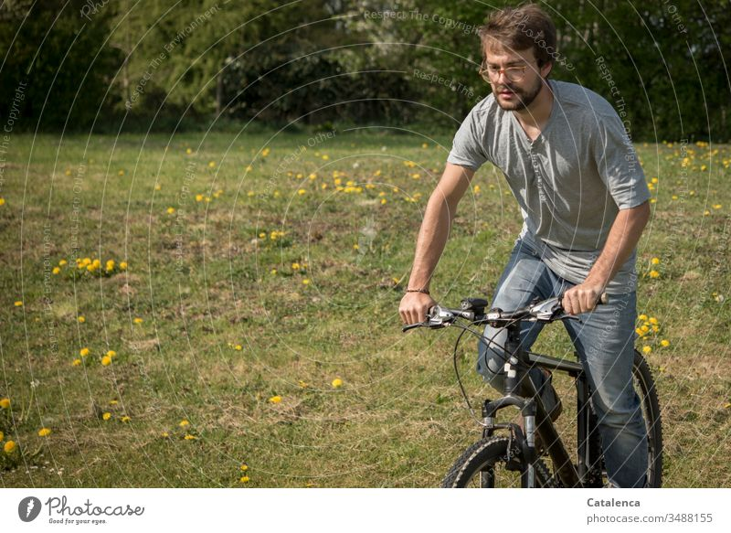 A young man rides his mountain bike onto a meadow dotted with dandelions Young man Masculine Human being 1 Mountain bike Bicycle Cycling Meadow Grass Dandelion