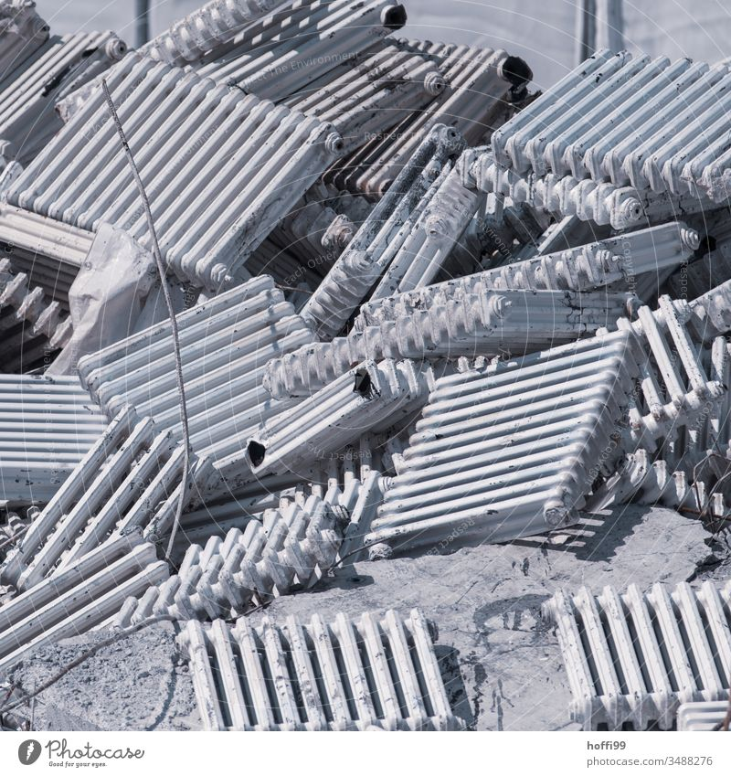 old radiators on a building site form a mountain Heater ribbed radiators Old modernise Heating Redevelop Construction site waste Disposal scrap metal Recycling