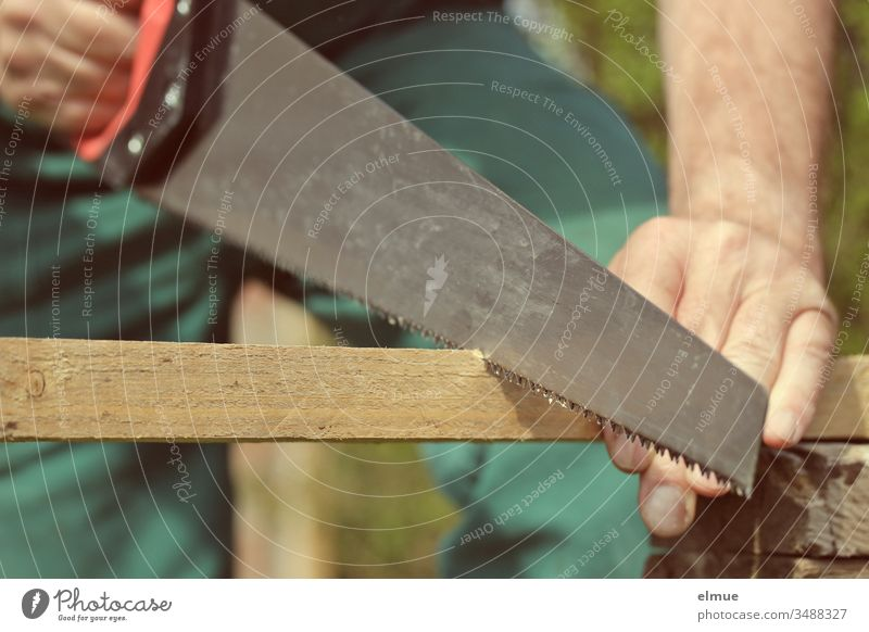 Man saws through a wooden slat with a foxtail - cutout Jacksaw Saw Tool Occupational health and safety Craftsperson to it yourself Hand Wood latte Craft (trade)