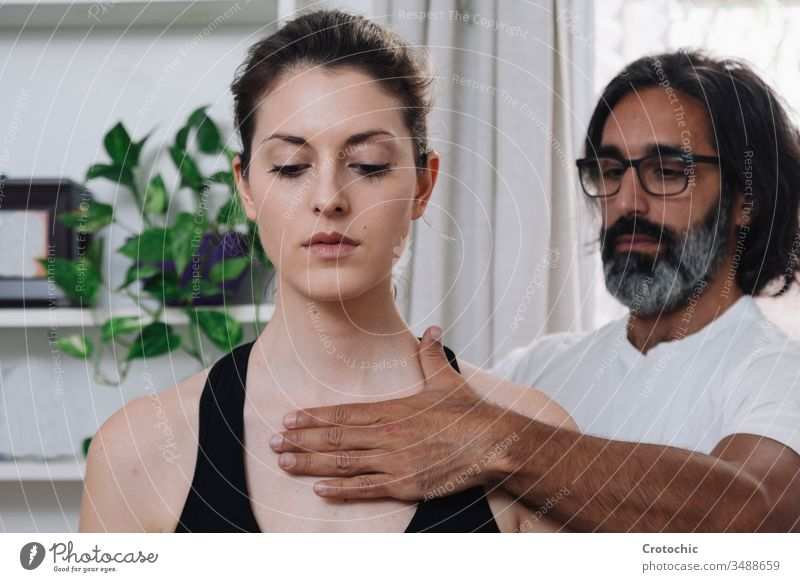 close-up of a beautiful woman being laid by a kinesiologist alternative aromatherapy arthritis back bodycare bone chiropractor clinic cosmetic dayspa doctor