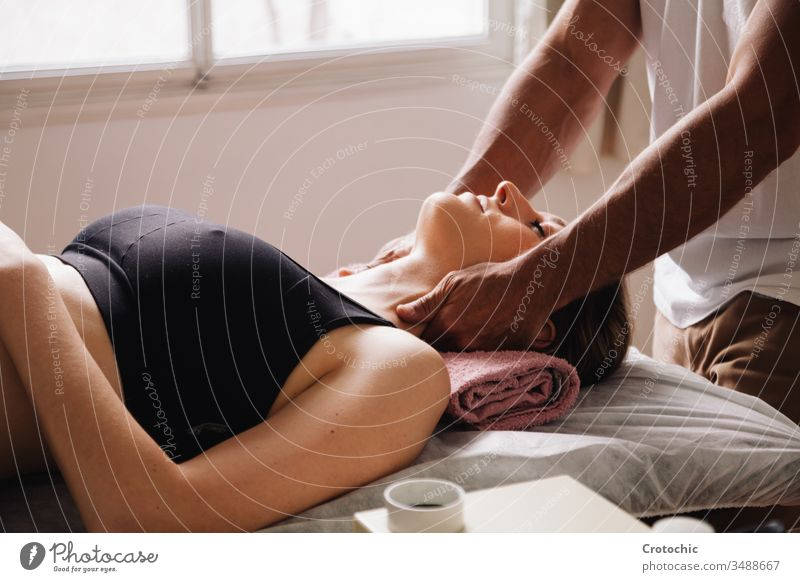 less than one masseur performing a neck massage to a beautiful woman lying down alternative aromatherapy arthritis back being bodycare bone chiropractor clinic