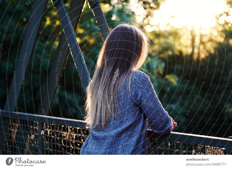 young woman stands alone at the bridge railing Woman Young woman on one's own Bridge railing Loneliness depression Fear of the future Rear view Unrecognizable