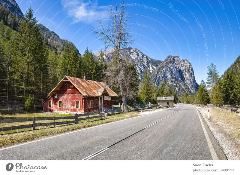 Red building on a road in an idyllic South Tyrolean landscape House (Residential Structure) Building Street mountains Forest Idyll Landscape Dolomites vacation