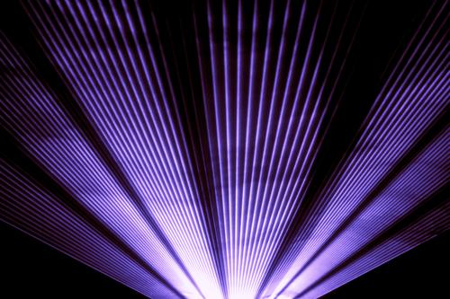 Purple laser show nightlife club stage shining sparkling rays. Luxury entertainment in nightclub event, festival, concert or New Years Eve. Ray beams are symbol for science and universe research