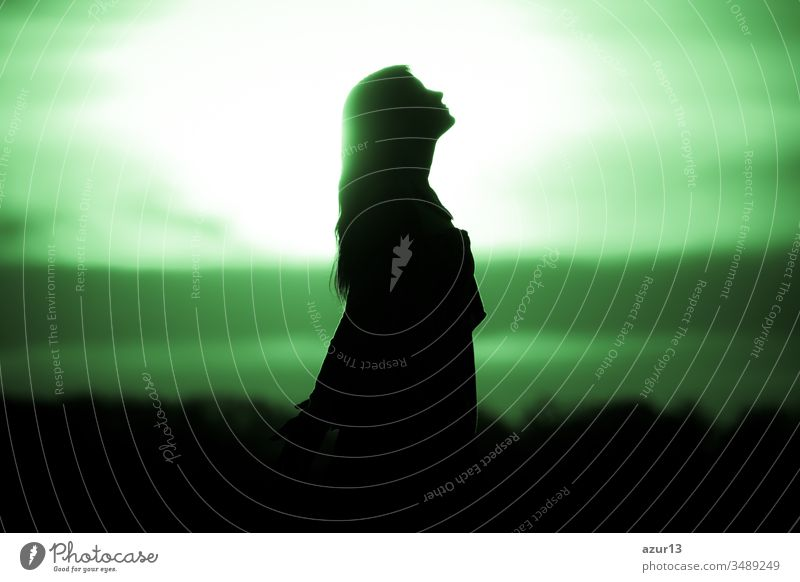 Youth woman soul at green sun meditation awaiting future times. Silhouette in front of sunset or sunrise in summer nature. Symbol for healing burnout therapy, wellness relaxation or resurrection
