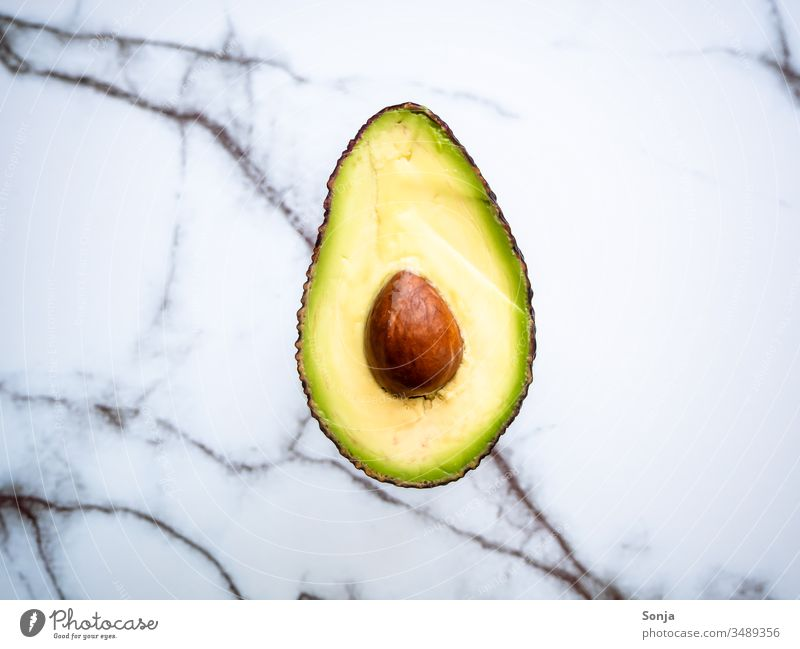 Halbierte Avocado mit Kern auf einem Marmorhintergrund, Draufsicht halbiert avocadokern marmor draufsicht Food Healthy Eating Vegetarian diet Fresh roh